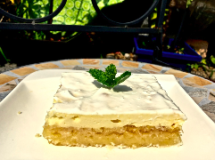 Kuchen mit Saurer Sahne bedecken und in Quadrate schneiden