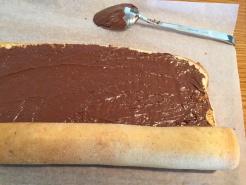 Biskuit mit Nuss-Nougat-Creme bestreichen und fest einrollen