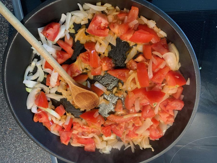 Klein geschnittene Tomaten, Mehl und Tomatenmark zufügen